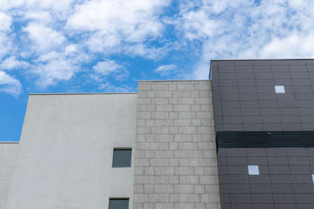 architecture simple background pattern exterior facade building design walls foreshortening from below with blue sky white clouds background space for your text here