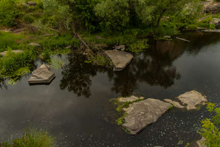 wilderness abandoned nature top view scenic environment space with pond waters stones and falling trees Фото со стока