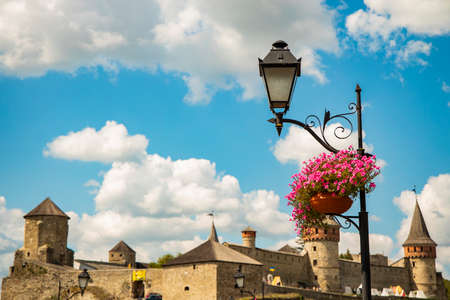 historical old city street lantern lamppost and blossom flower vase with medieval landmark tower architecture shape background view in clear weather day time