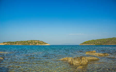 wilderness beach scenic view on two island shore line with Mediterranean sea bay summer day time landscape clear weather and empty blue sky background copy space
