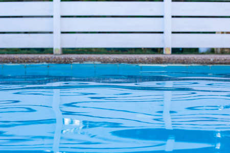 soft focus swimming pool side relaxation space blue water and garden white wooden deck fence background yard view copy space