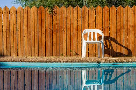 swimming pool site garden relaxation environment outdoor space without people here white chair and wooden wall background