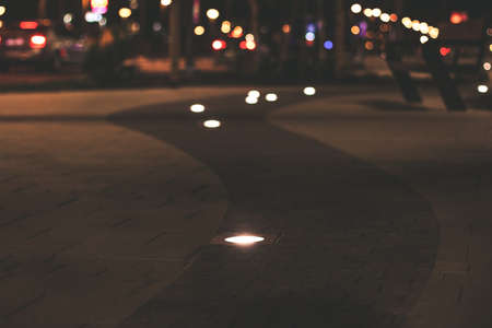 soft focus night street promenade walking alley paved road and lamps illumination with unfocused background urban