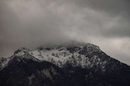 moody dramatic mountain landscape cloudy gray weather day time with Alps mountains snowy peak range copy space Фото со стока