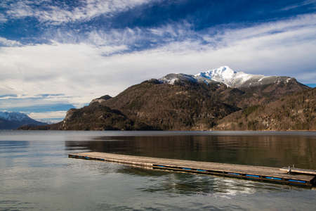 peaceful autumn landscape wooden pier on a lake shore line with moody scenic view of mountain snowy peak October fall season day time Фото со стока