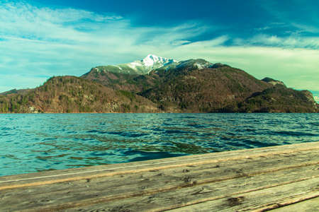 north Europe spring time landscape with mountain snowy peak background scenic view lake waters and wooden pier foreground space