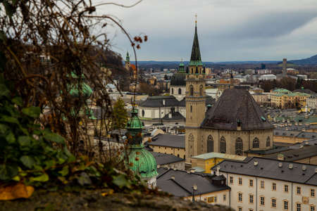 Austria Salzburg moody Europe city landmark view catholic cathedral tower and gray old buildings from above top view point in rainy autumn day time Фото со стока