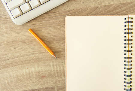 office simple background pattern with white paper notebook pencil and keyboard on table top view vintage style soft colors and empty copy space for your text here Фото со стока
