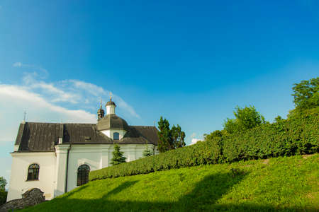 monastery church building Eastern European architecture summer landscape scenic view green grass meadow and blue sky background clear weather June day