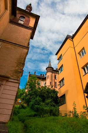 old city buildings urban landmark view vertical picture with tower background roof top in summer vivid colorful day time foreshortening from below