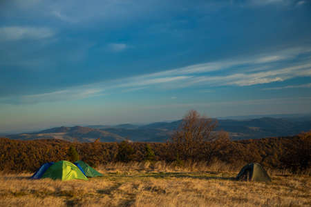travel life style landscape of tent camp side on highland meadow mountain forest nature scenery environment of autumn September season time Фото со стока