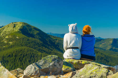 travel life style poster wallpaper photography of two sitting girls back to camera on rocks with summer time mountain landscape scenic view empty copy space for your text here