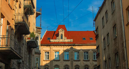 Eastern Europe old city street landmark urban view architecture exterior facade red roof building narrow alley way foreshortening from below with blue sky background in clear weather day time