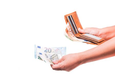 The hand takes out 20 euro money from the wallet. Hand sharing euro banknotes. Financial, money exchange and donation concepts. Wallet with euro. Banknotes Isolated on white background.