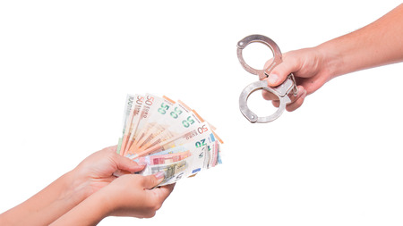 Human hand holding euro money and handcuffs. Fan of euro banknotes. Banknotes Isolated on white background. Stock Photo