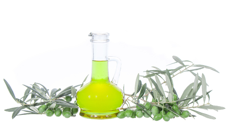 Glass bottle wtih extra virgin olive oil and olive branches. Olive tree brunch with olives isolated on white background. Natural and bio product. Greek olive oil with copy space. Stock Photo