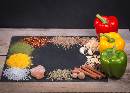 Spices, herbs and fresh pepper on slate tray on an old rustic table. Red, yellow and green fresh peppers. Top view. Rustic style. Fresh ingredients and vegetables for cooking.  Reklamní fotografie