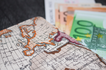 Money, Airplane ticket and map. Eurobanknotes with boarding pass and map, on black wooden background. Business and travel planning concept.  Stock Photo