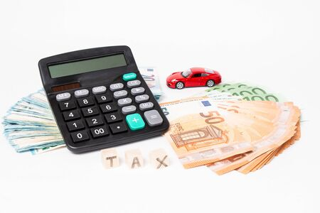 Calculator, euro money and red car. Wooden cubes with word tax. Red car and euro banknotes. Copy space for text. Tax and money payment.