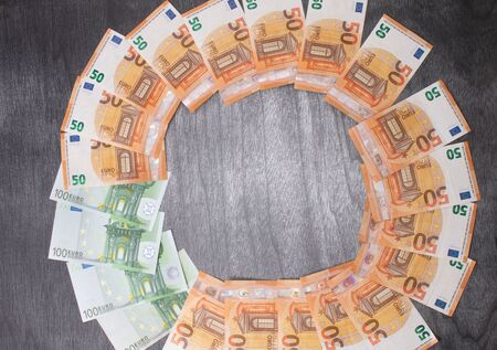Euro banknotes Laid out in a cicircle on a grey wooden background. Money finance earning sector concept. Copy space for text. Stack of money wealth, lottery prizes or banking crises.