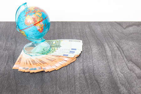 Globe on the desk and euro banknotes.  Money and globus on grey wooden desk. Euro money under globe of world. Copy space for text. Travel and money concept. Banco de Imagens