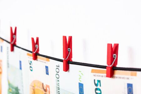 Euro banknotes hanging on a clothesline against white background. Euro money with red clothes pegs on rope. Money Laundering euro hung out to dry. Isolated euro money on string.