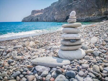 Symbolic scales of stones against the background of the sea and blue sky. Concept of harmony and balance. Pros and cons concept. Copy space for text.