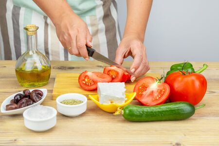 Woman cuts tomatoes for Greek salad. Ingredients for Greek Salad on wooden background. Healthy food, Mediterranean diet. Girl cooking Greek Salad with fresh vegetables.
