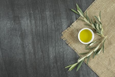 Top view of olive oil in a bowl, on wooden background. Olive oil with branches. Natural olive oil in white plate with branches around. Copy space for text or product.