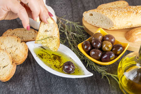 Woman dipping fresh bread into tasty olive oil with spices in bowl. Olive oil bread dip. Olive oil sauce in white bowl & Greek olives on wood background.