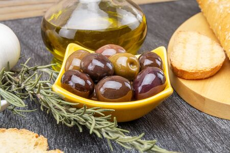 Close up of yellow bowl with olives and rosemary. Olive oil and bread on wooden background.