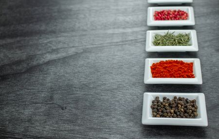 Spices and herbs on wooden table. Pepper, rosemary, tarragon, allspice, turmeric. Colorful spices in white bowls on grey background. Seasonings for cooking. Copy space for text.
