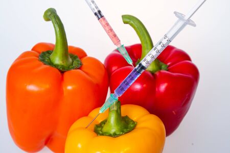 Genetically modified vegetables. GMO food concept. Syringes are stuck in vegetables with chemical additives. Injections into fruits and vegetables. Isolated on white background. Banco de Imagens