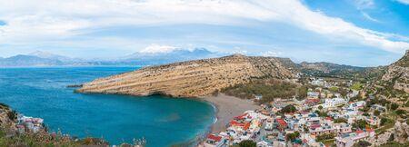 Panorama of Matala, beautiful beach on Crete island, waves and rocks. Matala village with caves and blue sky. Matala, Crete.