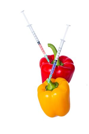 Genetically modified vegetables. GMO food concept. Syringes are stuck in vegetables with chemical additives. Injections into fruits and vegetables. Isolated on white background.