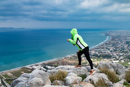 A young woman standing on a mountain and looking down. A girl stands and looks at the sea. A girl stands on a high mountain in the background of the city and the sea.  Banco de Imagens