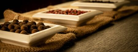 Bowl full of spices on burlap and a dark wooden background. Natural spices, vintage old seasoning theme.