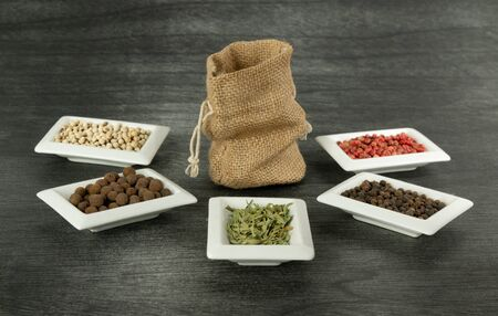 Burlap sack and natural spices on dark background. Jute Sack mock up and herbs. Copy space for text. Traditional Vintage Sack mock up. Linen sack copy space for product.