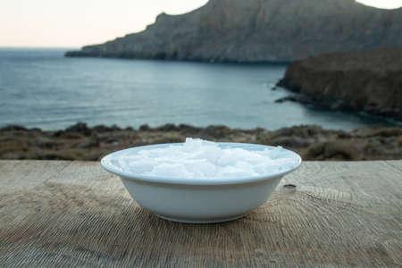 Flower of Greek sea salt crystals, south Crete. Natural traditional Fleur de sel from Crete. Sea salt flakes on wooden bakcground. Banco de Imagens