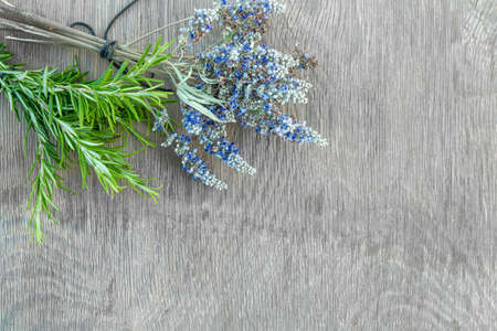 Beautiful Greek wild lavender and rosemary on natural wooden background. Copy space for text. Aromatherapy and essential oil concept. Space for you product.