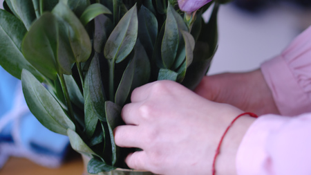 Putting beautiful flowers in a vase to further create a bouquet for a gift