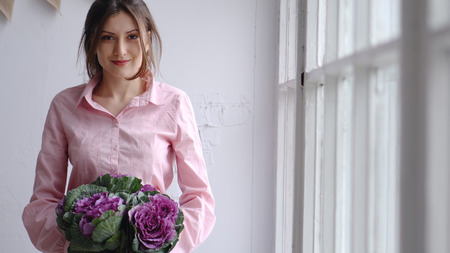 Portrait of a beautiful florist with a violet bouquet of unusual flowers - brassica. Look in the camera.