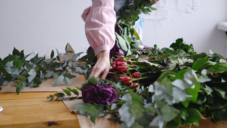 A woman florist is laying flowers at her workplace