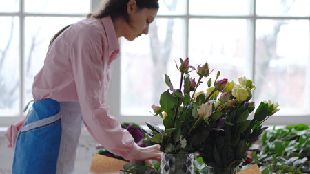 Florist at work: young woman making modern bouquet of different flowers