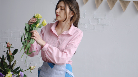 A Young Florist picks flowers eustoma and inspects them for her arrangement Stock Photo
