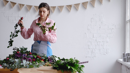 Concentrated young female florist creating a floral composition, inspect flowers