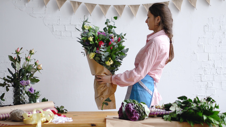 Florist check big modern bouquet of different flowers before sale