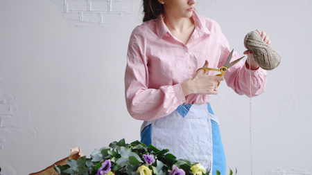 Front view of florist cuts a thread with scissors to arrange a bouquet
