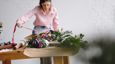 Female florist wrapping a bunch of flowers Banco de Imagens
