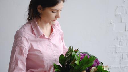 Florist girl check bouquet of different flowers